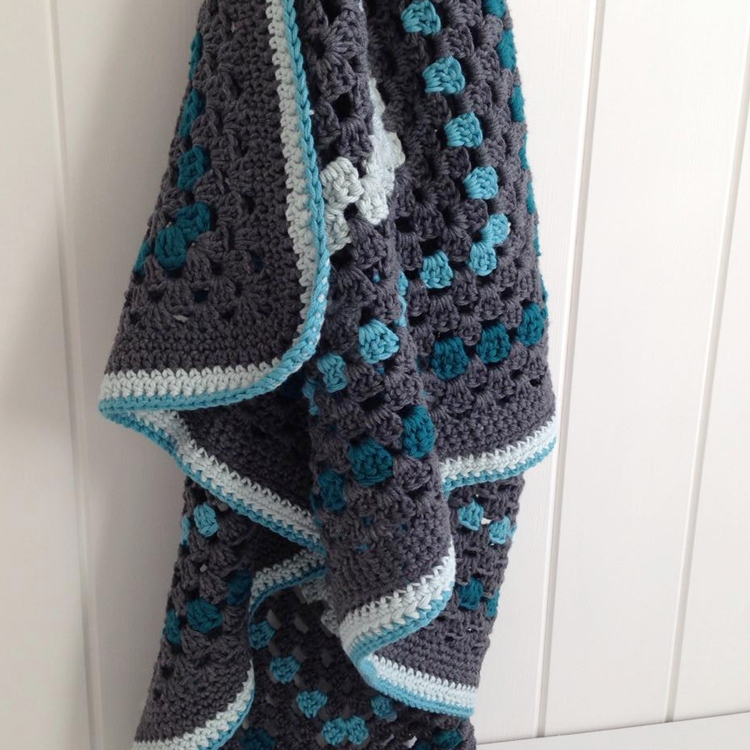 Grey granny square blanket hanging